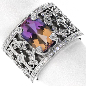 This large ametrine makes for a stunning center stone. The two tone nature of the stone is highlighted by the surrounding white gold and white diamonds. A unique engagement ring with antique inspired filigree patterns.