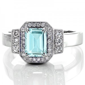 Stunning art deco style engagement ring featuring an aquamarine center stone. The micro pave halo and side bars are set with dazzling round dimaonds.