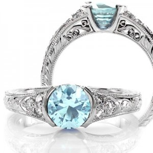 Unique engagement ring shown with aquamarine center stone in a half bezel setting. The band is detailed with hand formed filigree curls and hand engraved patterns.