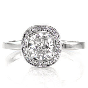 Low, flush, bezel set cushion cut diamond engagement ring design with a diamond halo
