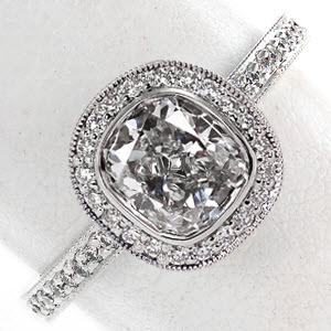 Bezel set cushion cut diamond engagement ring with diamond pave band