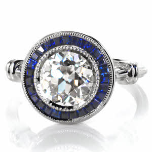 Custom engagement ring design created by Knox Jewelers featuring a blue sapphire halo around a 2.00 carat old european cut diamond.