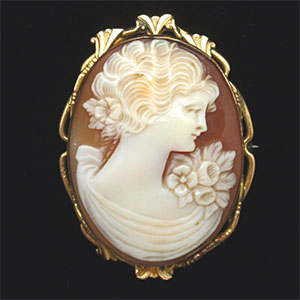 Yellow gold brooch freatures a helmet shell cameo of a woman's shillouette and floral accents.