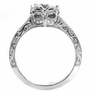 This platinum engagement ring feaures a crown inspired bezel and is detailed with diamonds and milgrain texture.