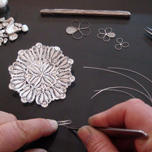 Individual strands of wire are hand formed into a specific pattern and are combined with others to create a beautiful design materpiece.