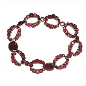 A stunning bracelet from the Georgian Era featuring custom cut red garnets that are fashioned in open to closed patterns.