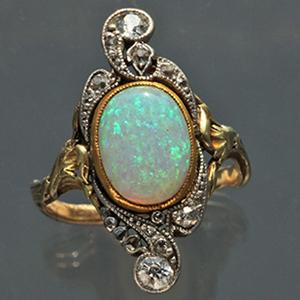 Antique ring featuring Art Nouveau era detailing including whiplash lines, bead-set diamonds and a center bezel-set opal.