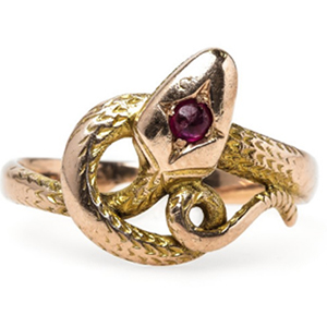 The the overlapping band twists and turns like the movement of a serpent and the center of the spepent's head fashions a round ruby gemstone.