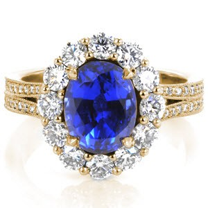 A striking Georgian inspired engagement ring is shown with a vibrant blue oval sapphire and surrounded by colorless round diamonds in a yellow gold setting.
