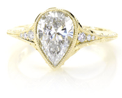 Antique engagement ring shown with a pear cut diamond in 18k Yellow Gold.