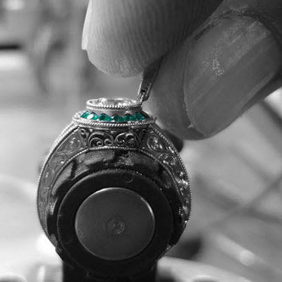 Master jeweler setting rolling milgrain onto a vintage styled oval center stone engagement ring.