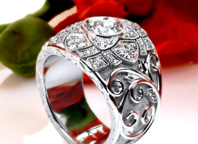 Custom wide band engagement ring in Victoria with a diamond set center floral design and hand engraved vine patterns.