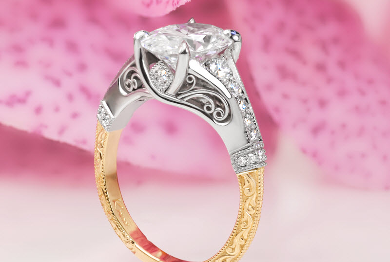 Calgary custom two tone engagement ring with an oval diamond held center by four prongs and a band featuring bead set diamonds, milgrain edging, filigree and relief engraving.