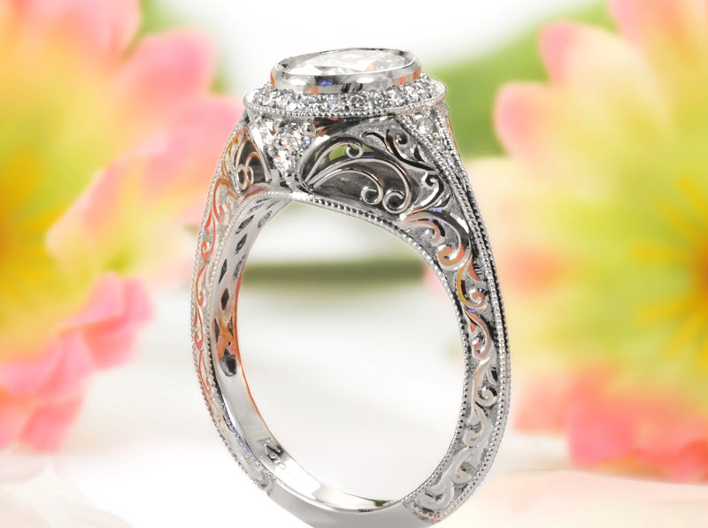 Antique inspired custom engagement ring in Calgary with an oval shaped center diamond surrounded by a diamond halo and a relief engraved band.
