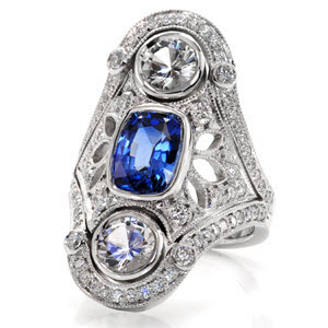 An elongated ring featuring a cushion cut royal blue sapphire and two round diamonds surrounded by an ornate pattern of pierced elements and milgrain.