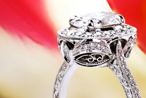 Antique inspired oval halo engagement ring with arching diamonds, filigree and hand engraving in Louisville.