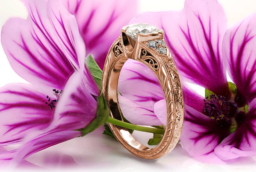 Portland rose gold engagement ring with half bezel round center stone, scroll filigree and hand engraving.