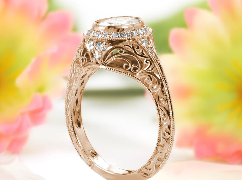 Vintage style rose gold engagement ring in St. Louis. The classically antique knife-edge band is hand engraved with relief style scroll patterns. Hand formed filigree curls detail the basket under the micro pave halo. A decorative rose gold lattice finishes the inside of the ring.