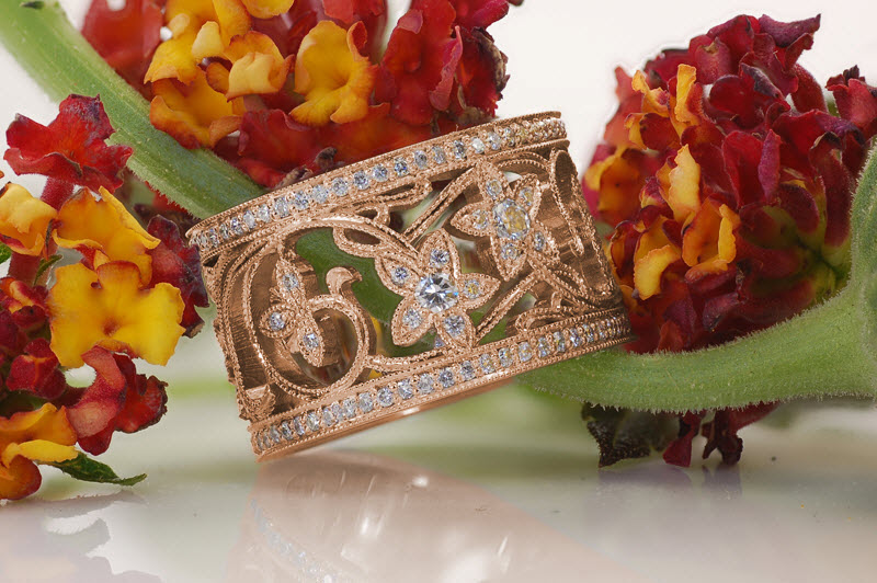 San Jose custom wide band rose gold engagement ring with bead set diamond rails bordering an intricate diamond set floral pattern.
