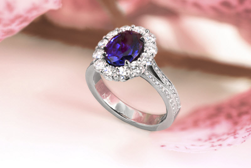 Gorgeous sapphire engagement ring in Tulsa with a large diamond halo. This stunning halo engagement ring design features micro pave diamonds adorning the underside basket of the halo. The blue oval cut sapphire center stone really pops!