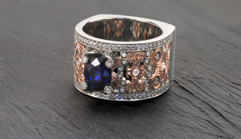 Stunning sapphire engagement ring in Portland features intricate, diamond set filigree patterns done in two-tone of rose gold and platinum. This wide design is framed with micro pave diamond rails.