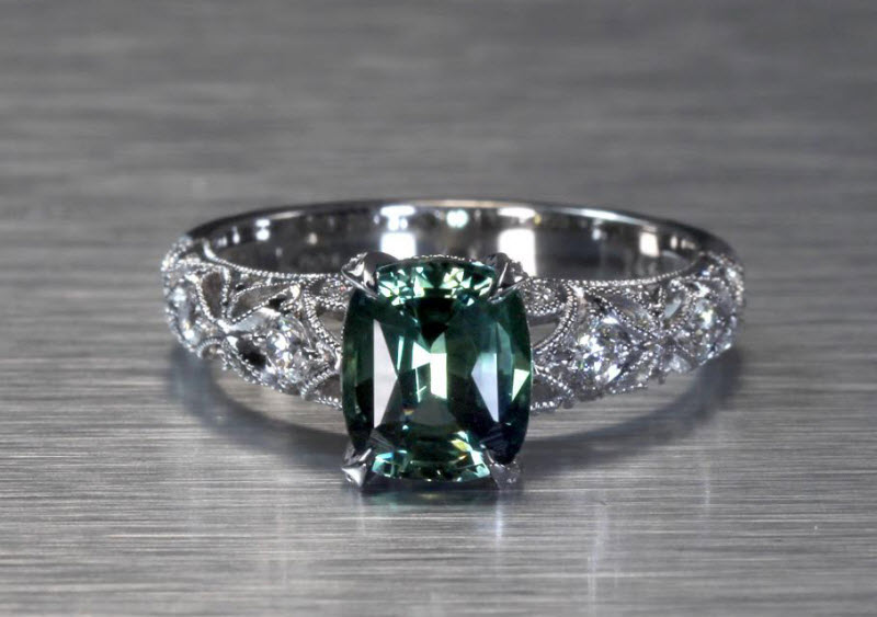 Stunning green-blue sapphire engagement ring in Denver. This antique engagement ring style features openwork starburst patterns set with micro pave diamonds. The rare blue-green cushion cut sapphire center stone is a perfect focal point.