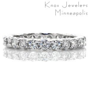 This sophisticated eternity band features a total of 1.44 carats of round brilliant cut diamonds. The stones are set with elegant, shared prong settings which minimize the amount of the diamond being covered by metal prongs. This design has a low profile and can be worn as a wedding or anniversary band.