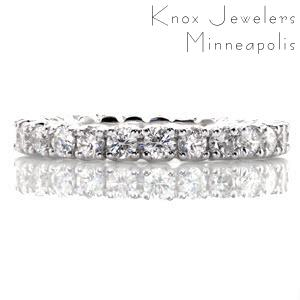 This graceful eternity band features a continuous row of round brilliant stones in four prong settings. The side profile reveals open sided settings that create a flowing, visual appeal. The ring totals 1.30 carats of vividly brilliant diamonds that will create a beautiful display in all light.