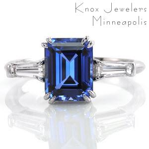 This stunning three stone engagement ring features a 2.00ct emerald cut blue sapphire center stone with a diamond baguette on either side.