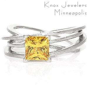 Design 1168 elegantly displays a 1.25 carat princess cut sapphire within four v-shaped prongs. Crafted in 14k white gold, the height of the multiple bands give the appearance of movement. The flow of the bands add interest which intensifies the vibrant hue of the natural yellow sapphire.
