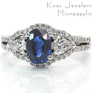 Regal engagement ring featuring a blue cushion cut sapphire center stone accented by a pear cut diamond on either side. This three stone design is then outlined by a split shank, micro pave band.