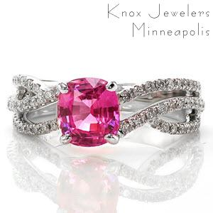 Adriana Sophia features a 1.84 carat cushion cut pink sapphire in a four prong setting. The vibrant pink hue is a striking pop of color in the shining 14k white gold setting. The micro pavé diamonds line the three woven bands to add brilliance and fire to the sapphire center.