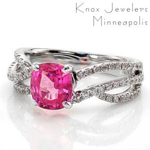 Custom pink sapphire engagement ring in Austin. This unique, micro pave split shank engagement ring features flowing diamond bands and a bright pink cushion cut sapphire center