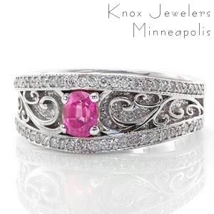 The Arabella sapphire ring features a 0.40 carat bright pink oval sapphire. Crafted in 14k white gold, high polished curvacious scrolls accent the hand stippling detail. The band edges are finished in milgrain and micro pavé diamonds. The wide vintage inspired band gradually tapers down for a comfortable fit.