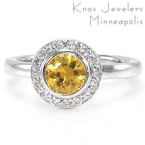 The luminous yellow of the sapphire center is a tantalizing vision to be seen. Micro pavé diamonds encircle the gemstone to enhance its beautiful golden hue. The sleek surface of the 14k white gold heightens the color of the delightful yellow sapphire.