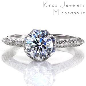 This unique ring features a pierced diamond shaped design that delicately cups the round 1.0 carat center stone. Micro pavé diamonds with a milgrain border add a decadent accent to the under bezel detail. A knife edge, double bead set diamond shank are a perfect finish with vintage flair.