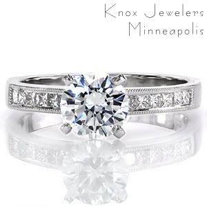 Simply stated, the Princess Petite design is crafted in 18k white gold. The band of gold frames channel set princess cut diamonds and outlined with hand applied milgrain. The 1.00 carat round brilliant cut center diamond is accented by four high polished prongs.