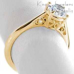 Unique yellow gold engagement rings in Baton Rouge. This elegant solitaire engagment ring has antique style inspirations shown by the expertly hand crafted filigree curls set in the basket and tapered band.