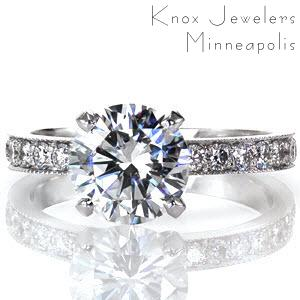 For an heirloom-quality classic style, look no further than the Pave Design. This exquisite piece features a 1.50 carat round brilliant center diamond set in a four prong crown. The band has simple, pleasing lines and micro pavé diamond detail. The edges of the band are detailed with milgrain.