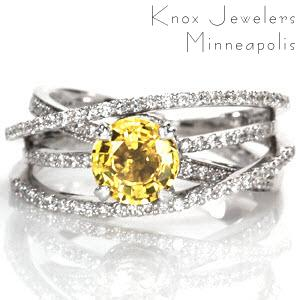 Design 1510 displays a mesmerizing sense of movement with four micro pavé bands. The height of the different bands create a perfect pocket for a unique 1.25 round yellow sapphire. The 14k white gold band wraps the natural sapphire in two micro pavé halos and is secured in a four prong basket.