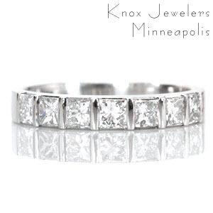 Design 1540 features 7 half-bezel set princess cut diamonds totaling 0.80 carats. Each square stone is fashioned in a single row along the band and is evenly spaced between a bar of metal. This high polished band pairs beautifully with a princess cut solitaire or by itself for a modern right hand ring.