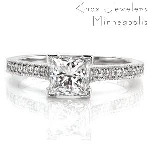 This charming design has a classic feel with the modern touch of a 1.00 carat princess cut center diamond. Chevron prongs are used to protect the corners of the princess cut. The micro pavé on the band goes all the way up the the sides of the cathedral setting to the edges of the center stone.