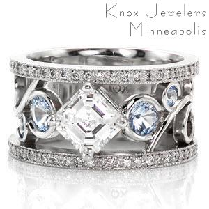 This unique wedding band features a 1.0 carat asscher cut center stone kite set within a four prong crown. The hand made filigree elements creates an alluring pattern that flows around six blue sapphires. The design is flanked by two rows of micro pavé diamonds for a sparkling finishing touch.