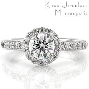 This lovely halo design accents the 0.75 carat four prong center stone perfectly. With decadently large, stunning, micro pavé diamonds, this design demands attention. The diamonds along the halo are set in a split-prong style bead setting, that is complimented by the bead set diamonds in the shank.