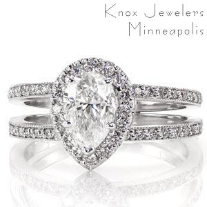 This luxurious design features a 1.00 carat pear cut center diamond surrounded by a halo. The split shank band and halo are both adorned with micro pavé that will dance with rainbow fire in any light. The edges of the band are textured with milgrain for a refined finish to an enthralling ring.