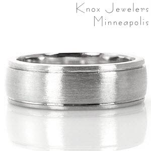 The Knox Jeweler's Seattle band is a modern gent's ring featured in 14k white gold. The long, narrow channel of the double pinstripe groove runs parallel to the edges of the ring. A brushed finish attractively adds texture to the surface of the design.