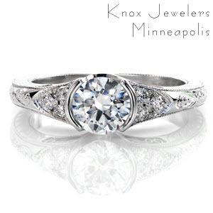 This is a vintage-inspired design that uses intricate details to accent the 0.75 carat round brilliant diamond. The center stone is bordered by a small triangular array of side stones for added embellishment. The exquisite handmade filigree and hand engraving gives it that heirloom-quality finish.
