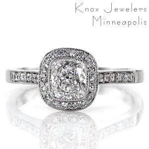 A splendid design with intriguing details, the Cushion Enchantment features a 0.75 carat, bezel set, cushion cut center diamond surrounded by a halo. The top of the band, the halo, and the underside of the halo are accented in micro pavé. There is a bezel set surprise diamond on each side.