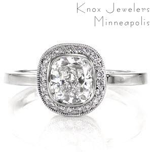 This delightful design is fully focused on the cushion shape. It features a 1.00 carat, bezel set, cushion cut center diamond surrounded by a halo of micro pavé which matches the shape of the center stone. The outer edge of the halo is detailed with milgrain to add texture and a refined finish.