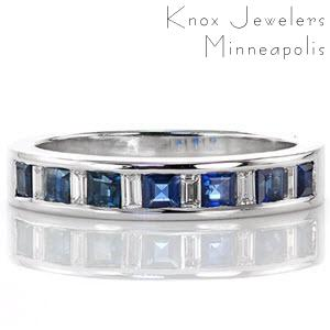This ring mesmerizes with its blue sapphire princess cut stones. The sapphires alternate with baguette cut diamonds which tie beautifully with the 14k white gold. The straight lines are carried throughout the design of the band for simple elegance. The cool tone of the stones and metal make for a sticking statement.